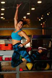 woman in blue sports bra jumping photo
