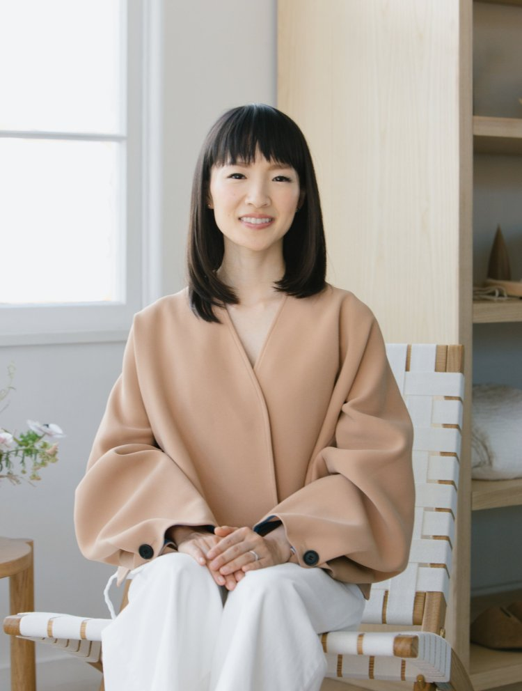 marie kondo sits on a chair in a clean house.